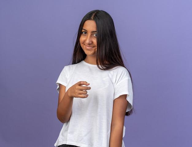 Jong meisje in wit t-shirt kijkend naar camera glimlachend vrolijk wijzend met wijsvinger naar camera staande over blauwe achtergrond