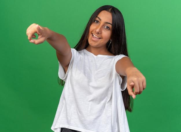 Jong meisje in wit t-shirt kijkend naar camera glimlachend vrolijk wijzend met wijsvingers naar camera staande over groene achtergrond