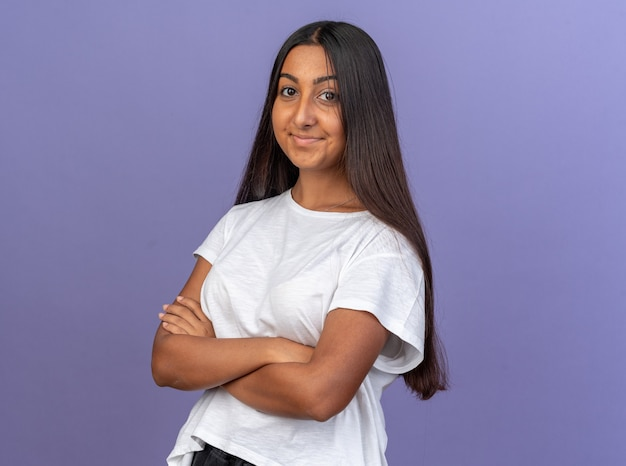Jong meisje in wit t-shirt kijkend naar camera glimlachend zelfverzekerd met gekruiste armen op borst staande over blauw