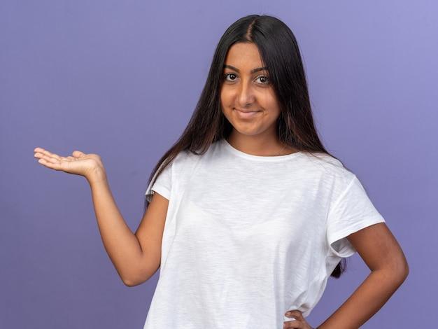 Jong meisje in wit t-shirt kijkend naar camera glimlachend zelfverzekerd presenterend kopieerruimte met arm van hand
