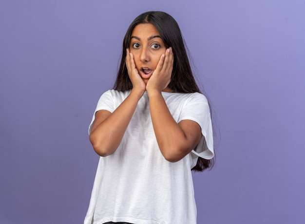 Jong meisje in wit t-shirt kijkend naar camera verbaasd en verrast over blauwe achtergrond