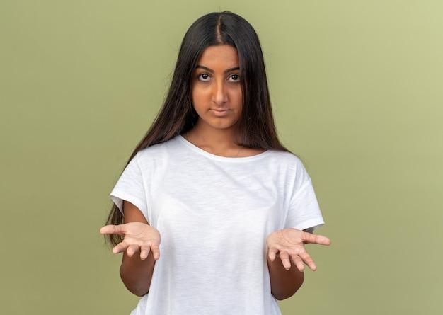 Jong meisje in wit t-shirt kijkend naar camera verward armen opstekend in ongenoegen en verontwaardiging staande over groen