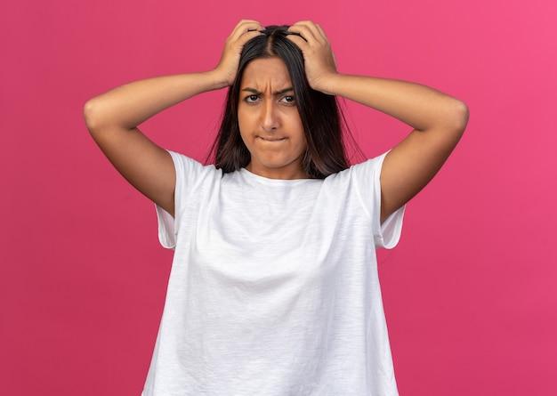 Jong meisje in wit t-shirt kijkend naar camera verward en erg angstig met handen op haar hoofd over roze