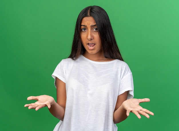 Jong meisje in wit t-shirt kijkend naar camera verward en ontevreden met opgeheven armen in ongenoegen en verontwaardiging