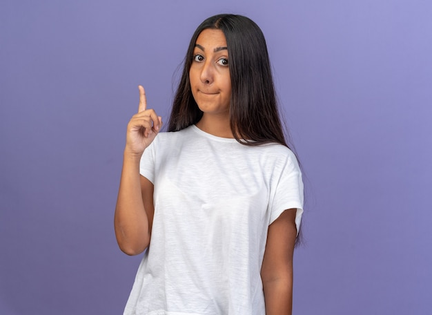 Jong meisje in wit t-shirt kijkend naar camera verward wijzend met wijsvinger omhoog staande over blauw