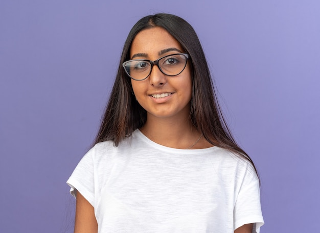 Jong meisje in wit t-shirt met een bril die naar de camera kijkt met een glimlach op een blij gezicht