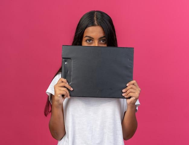 Jong meisje in wit t-shirt met klembord voor haar gezicht kijkend naar camera