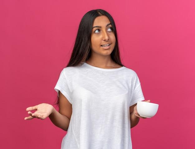 Jong meisje in wit t-shirt met kopje koffie opzoeken met een glimlach op het gezicht staande over roze standing