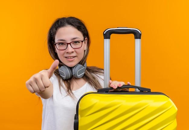 Jong meisje in wit t-shirt met koptelefoon rond nek houden reiskoffer glimlachend duimen opdagen