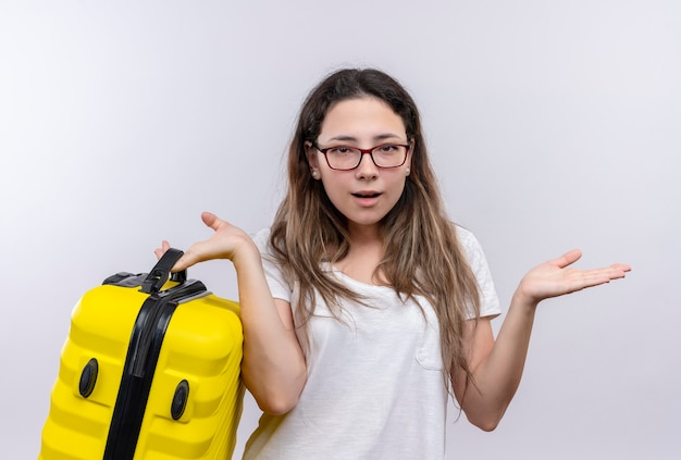 Jong meisje in wit t-shirt met reiskoffer op zoek onzeker en verward spreidende palmen
