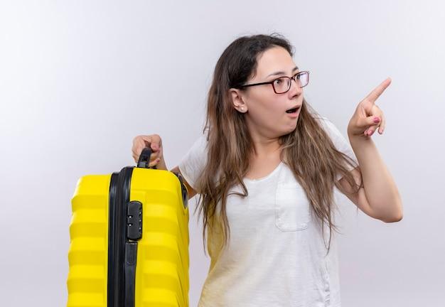 Jong meisje in wit t-shirt met reiskoffer opzij kijken verrast en verbaasd wijzend met wijsvinger naar iets