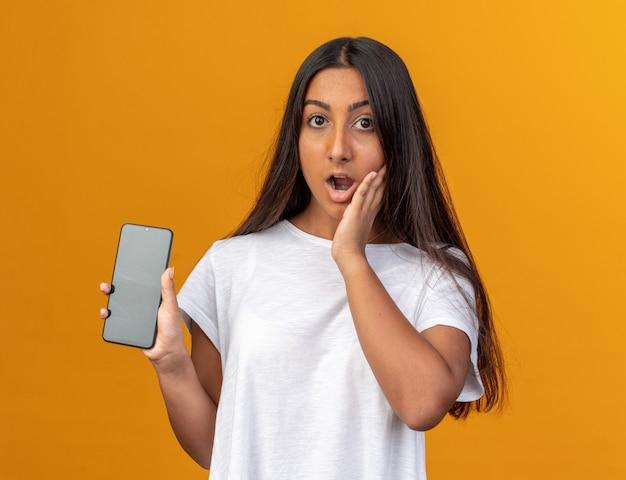 Jong meisje in wit t-shirt met smartphone die verbaasd en verbaasd naar de camera kijkt terwijl ze over oranje achtergrond staat