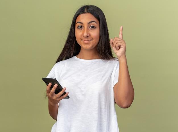 Jong meisje in wit t-shirt met smartphone kijkend naar camera met glimlach op slim gezicht