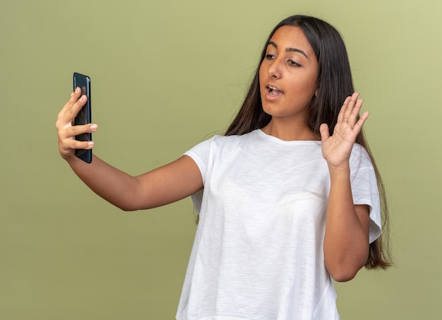 Jong meisje in wit t-shirt met videogesprek met smartphone glimlachend zwaaiend met de hand