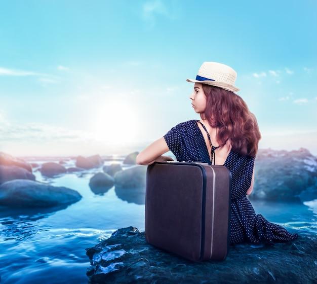 Jong meisje in witte hoed en zwarte jurk met koffer zit op een steen aan de oceaankust. heldere lucht op de achtergrond.