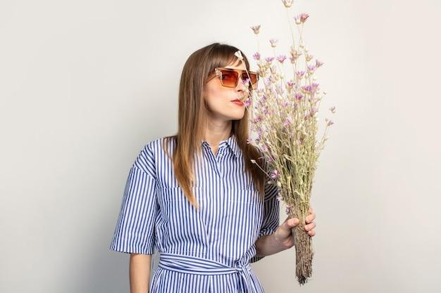 Jong meisje in zonnebril houdt een boeket wilde bloemen, snuift, geniet van de geur van bloemen, op een licht oppervlak