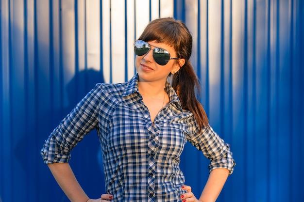 Jong meisje in zonnebril in shirt op blauw
