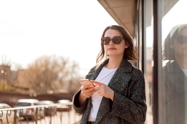 Jong meisje in zonnebril met een smartphone op straat