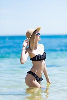 Jong meisje in zwarte bikini spelen in het water.