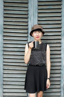 Jong meisje in zwarte jurk genietend van een kopje koffie in de middag