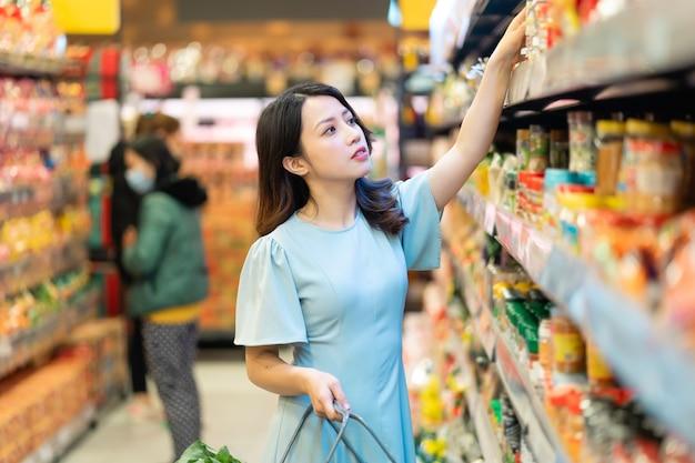 Jong meisje kiest ervoor om levensmiddelen te kopen in de supermarkt