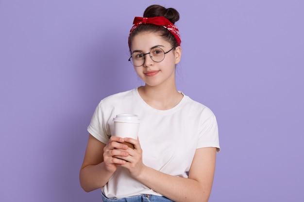 Jong meisje kijkt gelukkig, houdt haar warme koffie vast en