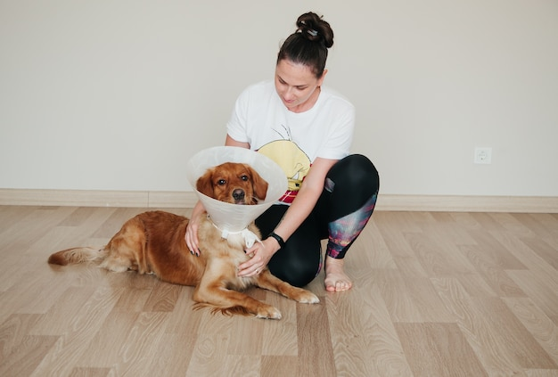 Jong meisje kijkt naar haar hond golden retriever met elizabethaanse plastic cone. geneeskundeconcept voor huisdieren