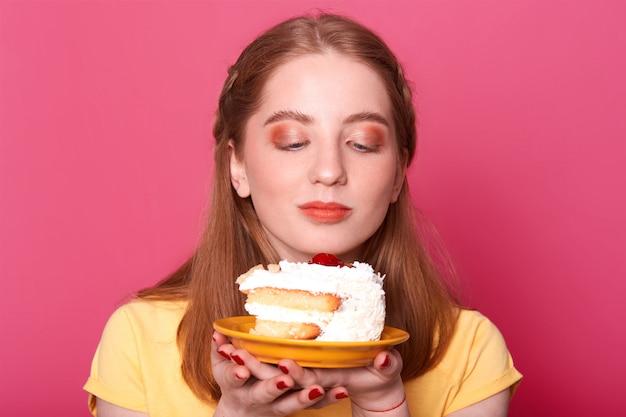 Jong meisje, kijkt naar plaat met stuk verjaardagstaart geïsoleerd op roze, wil lekker dessert eten, draagt gele t-shirt, heeft perfecte kapsel, poses.