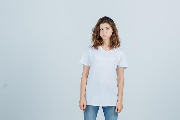 Jong meisje kijkt opzij, waait wangen in wit t-shirt en kijkt teleurgesteld. vooraanzicht.