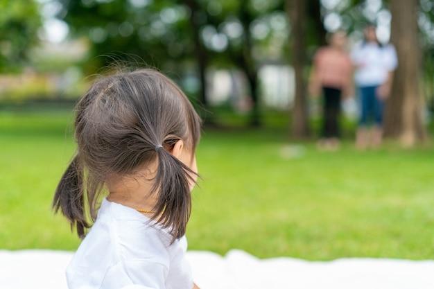 Jong meisje kijkt terug naar haar ouder die ver weg staat terwijl ze op de witte mat in de tuin speelt.