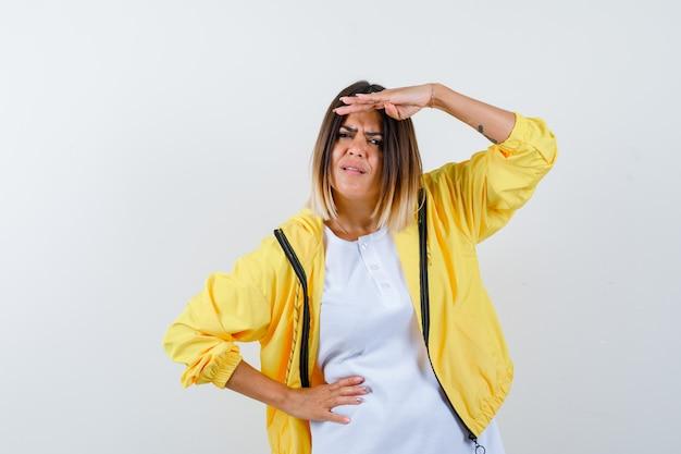 Jong meisje kijkt ver weg met hand boven het hoofd, houdt hand op taille in wit t-shirt, geel jasje en kijkt gefocust. vooraanzicht.
