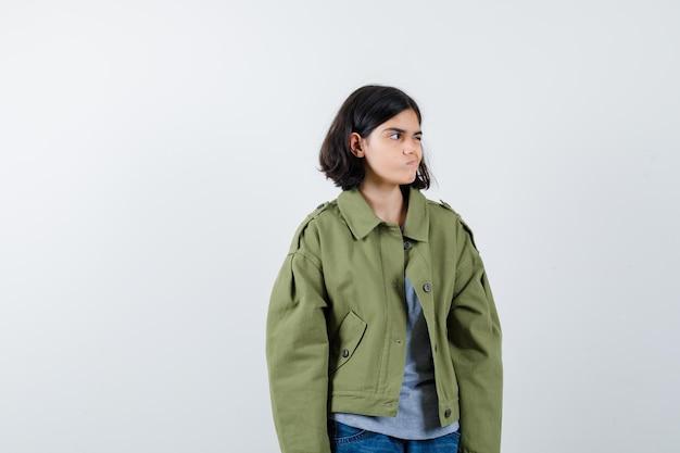 Jong meisje kijkt weg terwijl ze poseert in grijze trui, kaki jas, jeansbroek en serieus kijkt, vooraanzicht.