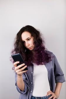 Jong meisje kijkt zorgvuldig in telefoon