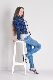 Jong meisje kind zittend op een stoel. glimlach vreugde emoties op haar gezicht. meisje in jeans die op lichte achtergrond stellen