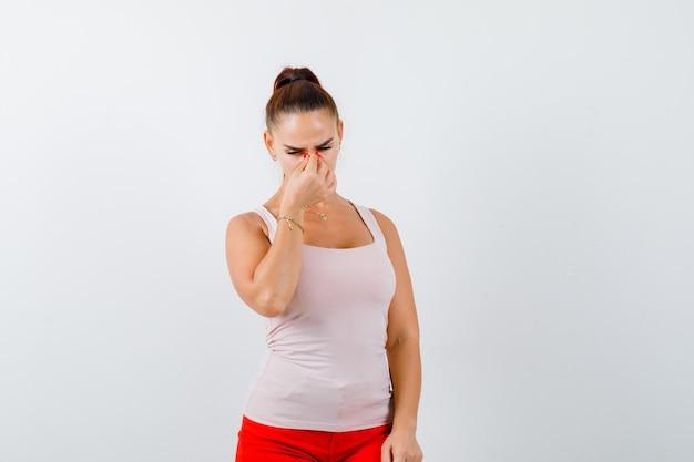 Jong meisje knijpen neus als gevolg van slechte geur in beige top en rode broek en op zoek geïrriteerd, vooraanzicht.