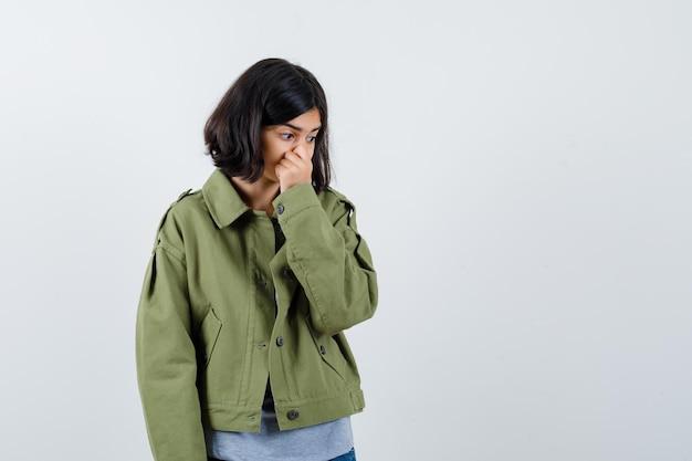 Jong meisje knijpt neus als gevolg van slechte geur in grijze trui, kaki jas, jeansbroek en kijkt gehaast, vooraanzicht.