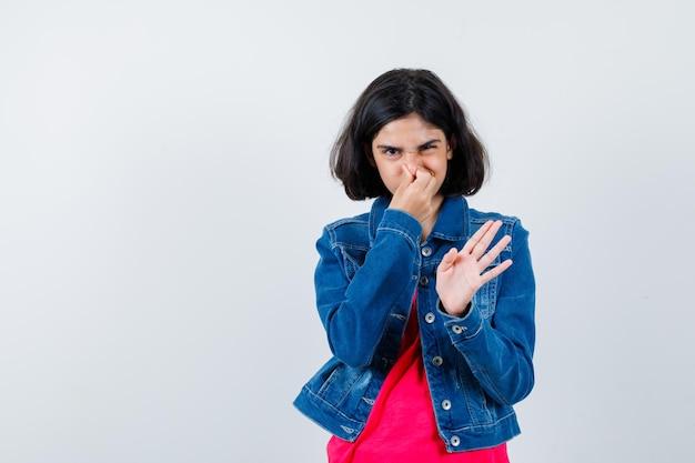 Jong meisje knijpt neus als gevolg van slechte geur in rood t-shirt en spijkerjasje en ziet er gehaast uit.