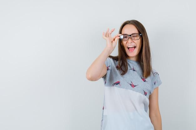 Jong meisje knipogen oog met vingers op bril in t-shirt en op zoek gek, vooraanzicht.