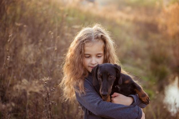 Jong meisje knuffelen zwarte hond buitenshuis