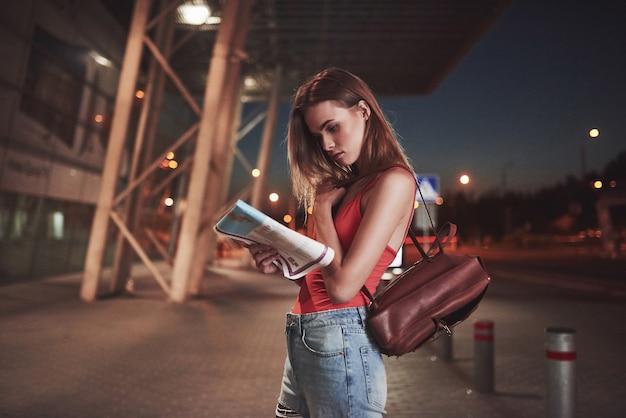 Jong meisje kost 's nachts in de buurt van de terminal van de luchthaven of het station en leest stadsplattegrond en zoekt hotel. leuke toerist met rugzakken bepalen het concept van reizen.