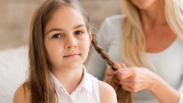 Jong meisje krijgt haar haar gevlochten door haar moeder