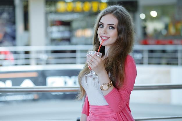 Jong meisje lachend met een frisdrank in een hand