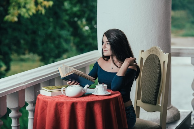 Jong meisje leesboek terwijl het drinken van koffie bij zonnige dag zittend op het balkon.