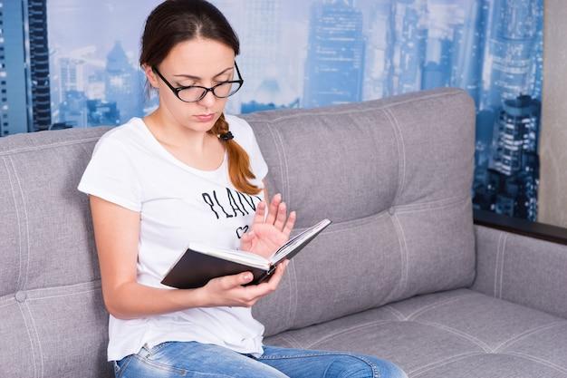 Jong meisje leest boek en draagt een bril zittend op een bank in de woonkamer in een ontspannen sfeer