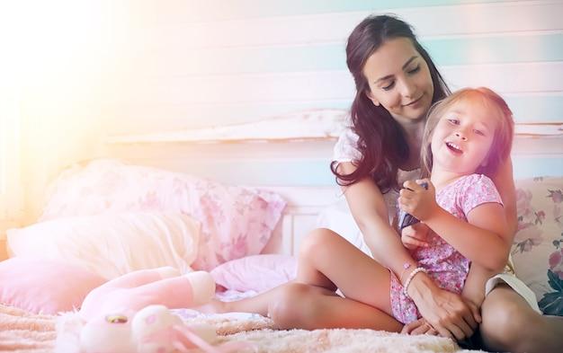 Jong meisje leest een boek jong meisje met een dochter zitten op het bed. zomerhuis in het dorp bij de tuin. rest van een jonge moeder en dochter in het dorp.