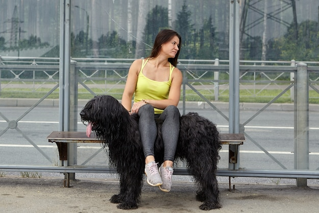 Jong meisje legde haar benen op zwarte briard terwijl ze op het station van het openbaar vervoer zat en op de bus wachtte.