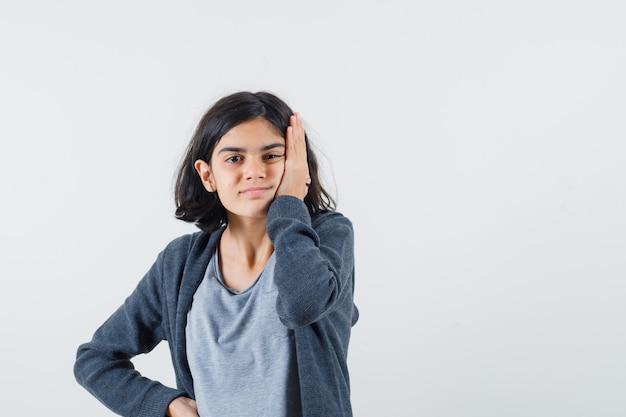 Jong meisje leunend met wang op handpalm, hand op taille in lichtgrijs t-shirt en donkergrijze hoodie met ritssluiting en ziet er schattig uit,
