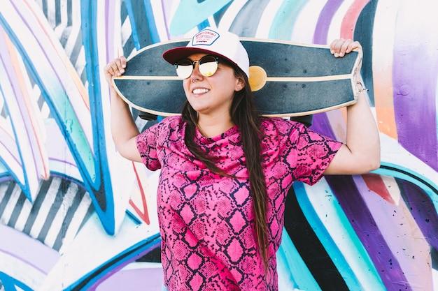 Jong meisje leunend tegen een muur met graffiti, met haar skateboard