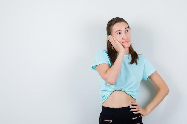 Jong meisje leunende wang op de palm, met de hand op de taille in turquoise t-shirt, broek en attent, vooraanzicht.