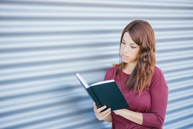Jong meisje lezen op een cover zwart boek op straat